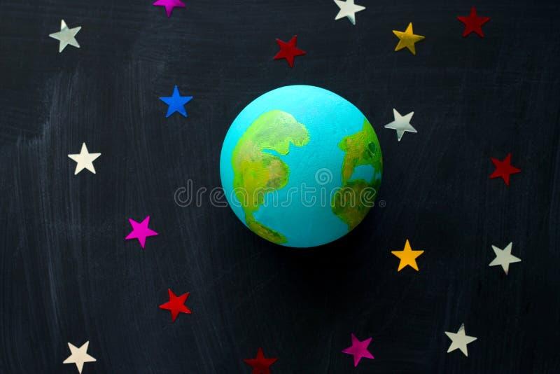 handgemachtes Modell des Erdplaneten und der Paillette in Form der Sterne auf dem Tafel-, Raum- und Astronomiekonzept stockbild