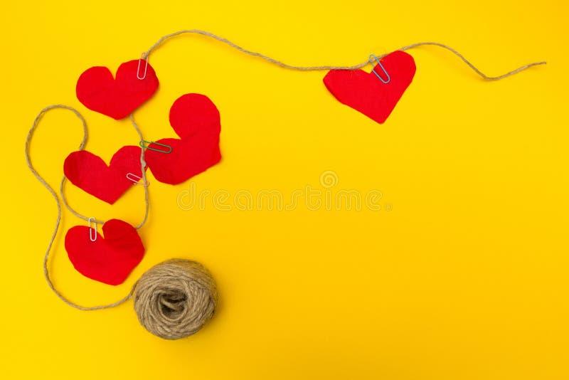 Handgemachtes Seil von fünf roten Herzen, gelber Hintergrund Flache Zusammensetzung stockbilder