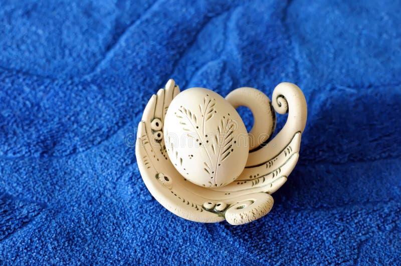 Handgemachtes weißes gemaltes Lehm Osterei in einem Nest auf einem blauen Hintergrund lizenzfreie stockbilder