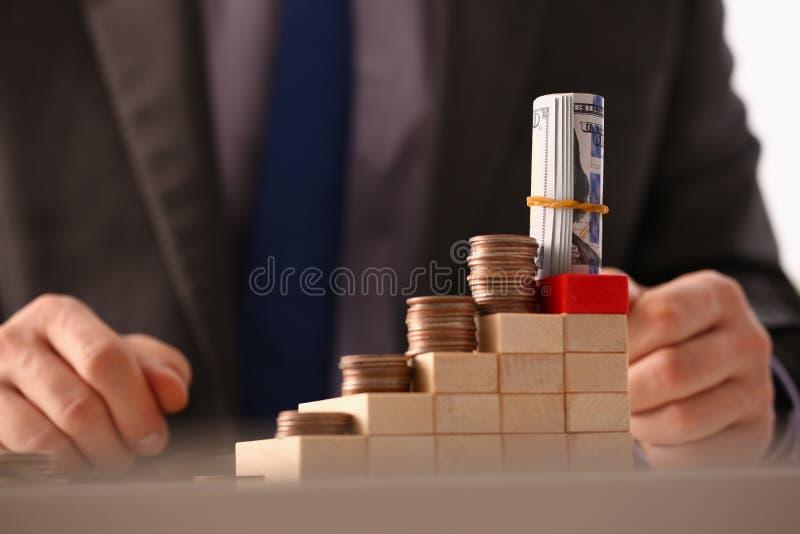 Handgeschäftsmann, der Stiftgeld steckt stockfotos