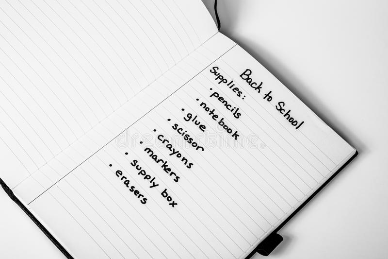 Handgeschriebene Einkaufsliste zurück zu des Schulbedarfs stockfotografie