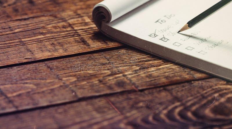 Handgeschriebene Liste von Angelegenheiten in einem Notizbuch auf rustikalem Schreibtisch, Nahaufnahme lizenzfreie stockbilder