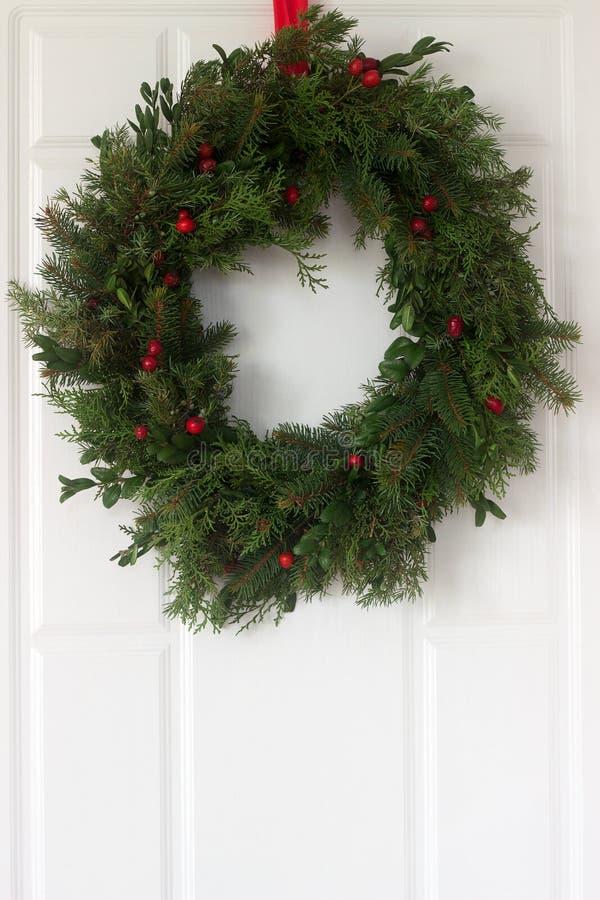 Handgjord är en julkrans som göras av granen, thujaen, en, buxbom och lösa rosa bär som smyckar ytterdörren arkivfoto