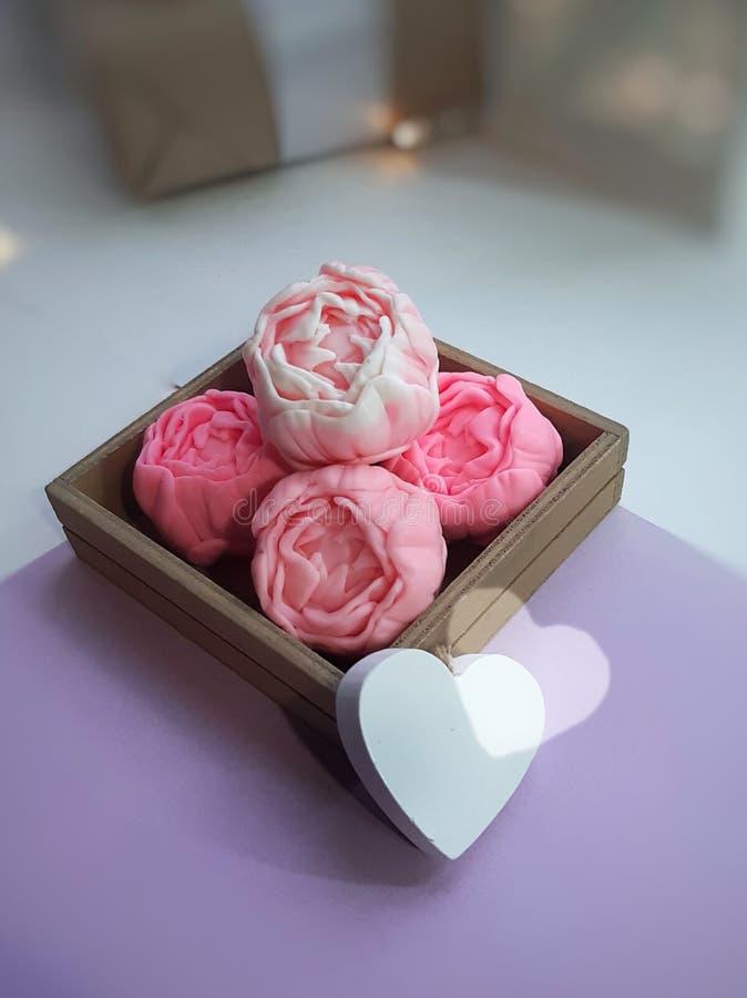 Handgjord blom- tvål i ask och trähjärta på romantisk bakgrund arkivfoto