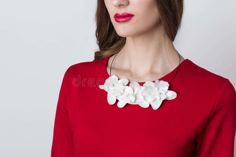 Handgjord blommaorkidé för härlig halsband på halsen av flickan på en vit bakgrund arkivbild