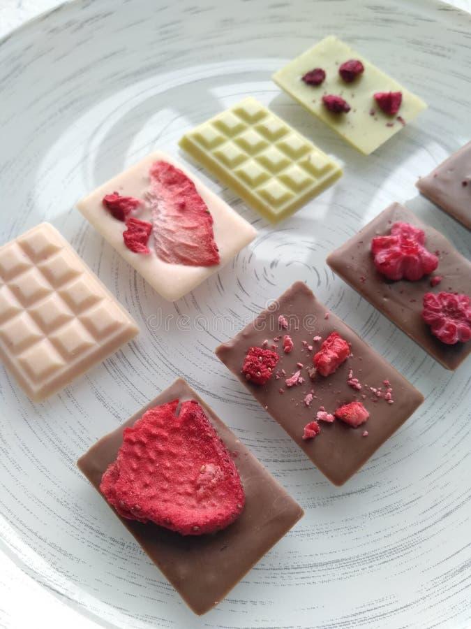 Handgjord choklad: mjölka choklad, jordgubbechoklad och vit choklad med matcha royaltyfria bilder