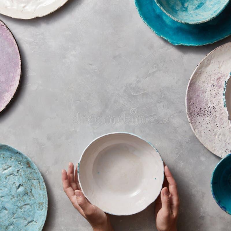 Handgjord disk för färgrik porceaintappning på en marmortabell med copyspace Kvinnahänder tar en vit keramisk bunke överkant royaltyfria foton