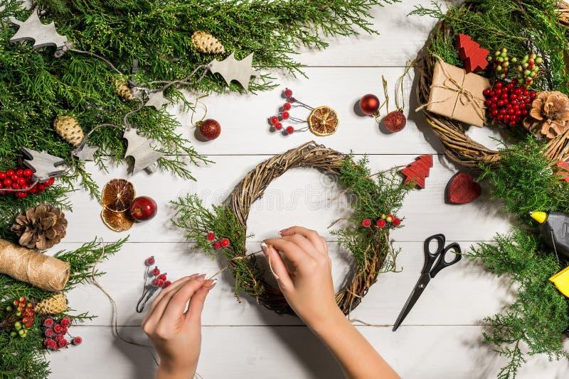 Handgjord diy bakgrund för jul Framställning av av hantverkxmas-kransen och prydnader Bästa sikt av den vita trätabellen med kvin royaltyfri fotografi