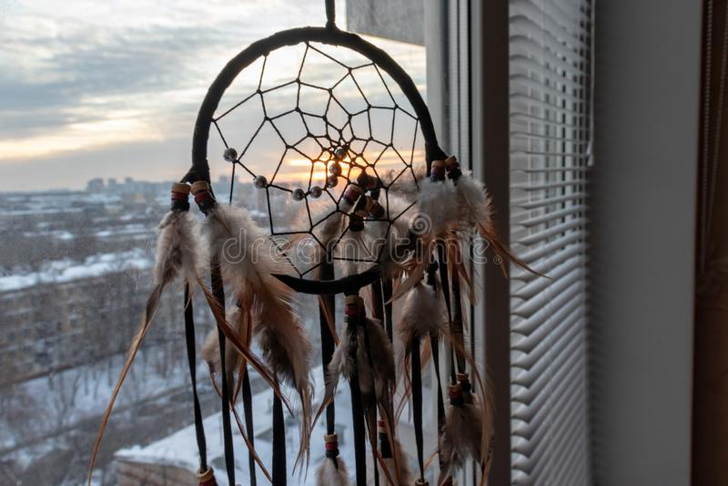 Handgjord dreamcatcher som hänger vid fönstret i soluppgångskymning Stads- stadslandskap på dackground Svart kontur av arkivfoton