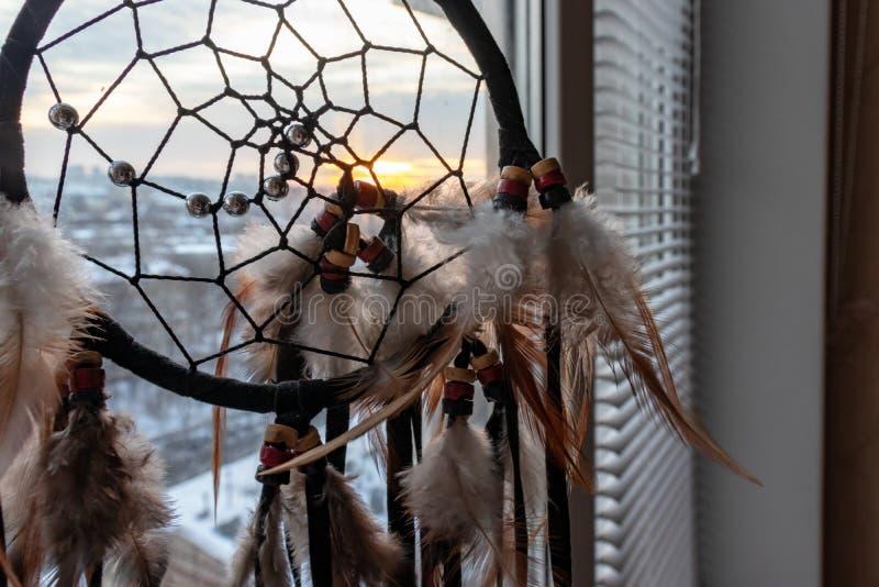 Handgjord dreamcatcher som hänger vid fönstret i soluppgångskymning Stads- stadslandskap på dackground Svart kontur av arkivfoto