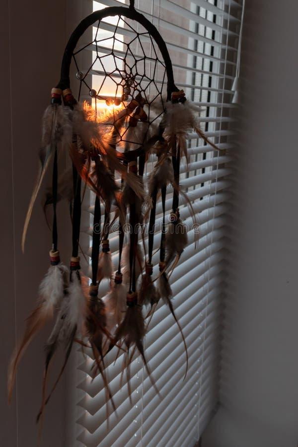 Handgjord dreamcatcher som hänger vid fönstret med rullgardiner i solnedgångskymning Svart kontur av den traditionella magiska am arkivbild