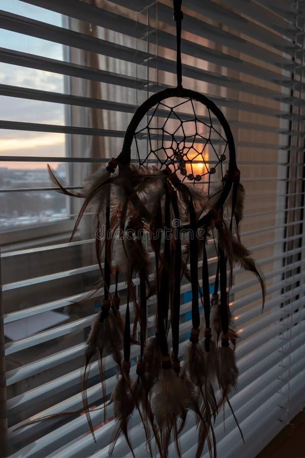 Handgjord dreamcatcher som hänger vid fönstret med rullgardiner i solnedgångskymning Svart kontur av den traditionella magiska am royaltyfri bild