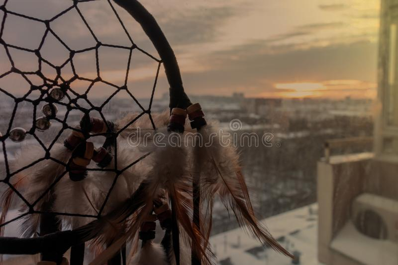 Handgjord dreamcatcher som hänger vid fönstret med rullgardiner i solnedgångskymning Svart kontur av den traditionella magiska am royaltyfri fotografi