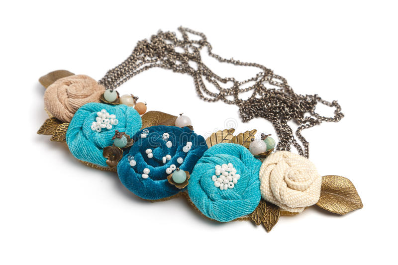Handgjord halsband i form av flera blommor av cyan, blåa och beigafärger royaltyfria foton