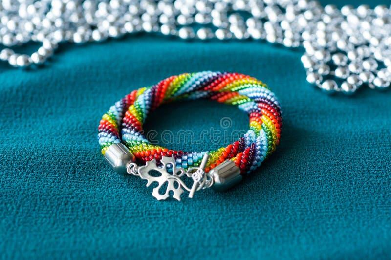 Handgjord mång--färgad halsband på en textilbakgrund royaltyfri foto