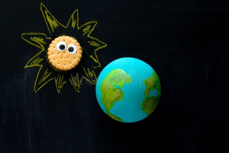 handgjord modell av jordplanet- och kakaSunwith roliga googly ögon på det svart tavla-, utrymme- och astronomibegreppet royaltyfria foton