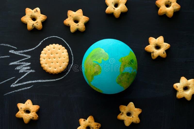 handgjord modell av jordplaneten, kakameteoriten och kakor i formen av stjärnor på den svart tavlan, utrymme och royaltyfri foto