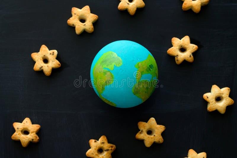 handgjord modell av jordplaneten och kakor i formen av stjärnor på det svart tavla-, utrymme- och astronomibegreppet royaltyfri bild