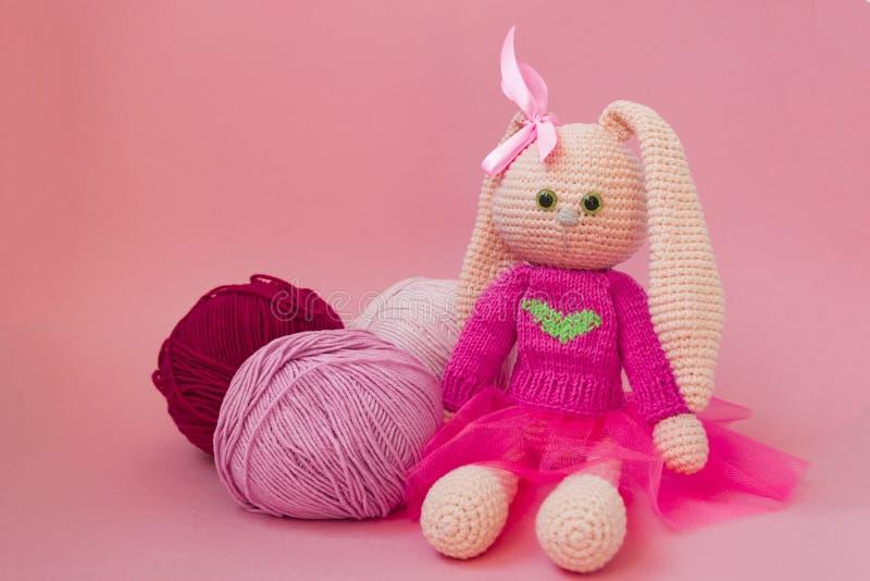 Handgjord stucken rosa kanin Påskkanin, i en rosa stucken tröja och i en rosa kjol Sitter bland garnnystan och rosa färger royaltyfri foto
