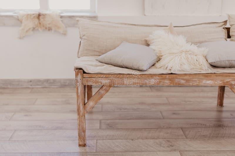 Handgjord träsoffa i ljust rum, mjuka kuddar royaltyfri foto
