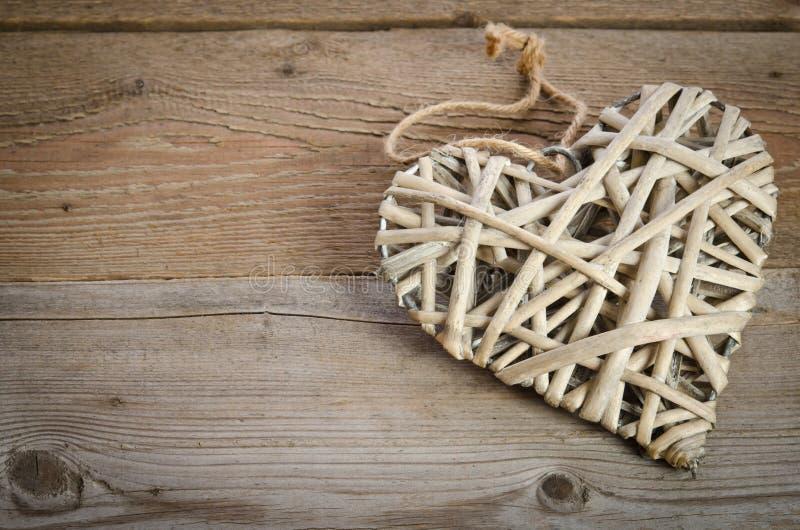 Handgjord vide- hjärta på en trägrund royaltyfria bilder