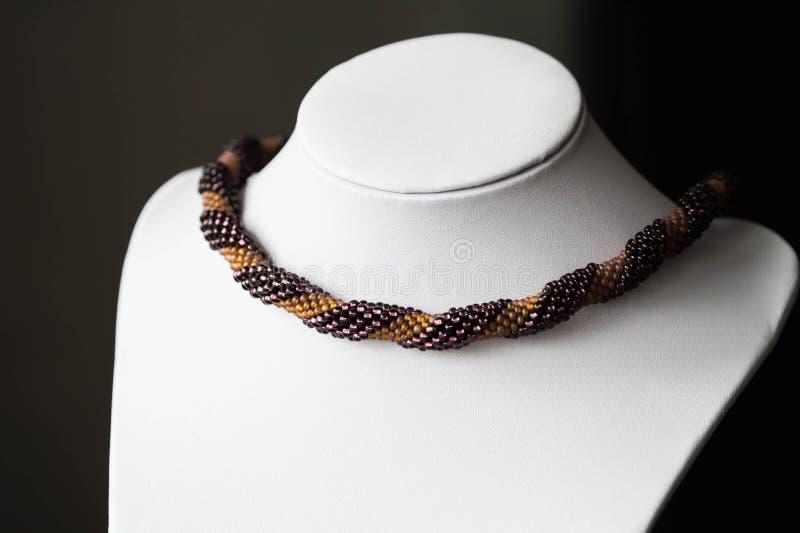 Handgjord virkad halsband som göras av pärlor av två färger royaltyfria bilder