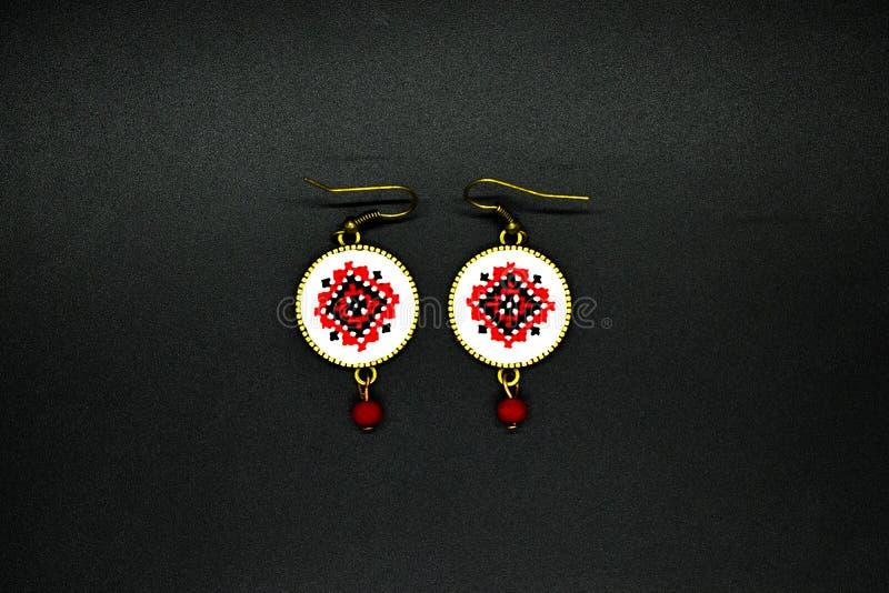 Handgjorda örhängen med den röda och svarta romanian traditionella modellen Isolerat på svart arkivfoto