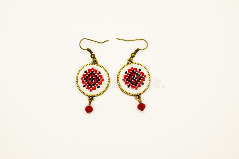 Handgjorda örhängen med den röda och svarta romanian traditionella modellen Isolerat på vit arkivfoton