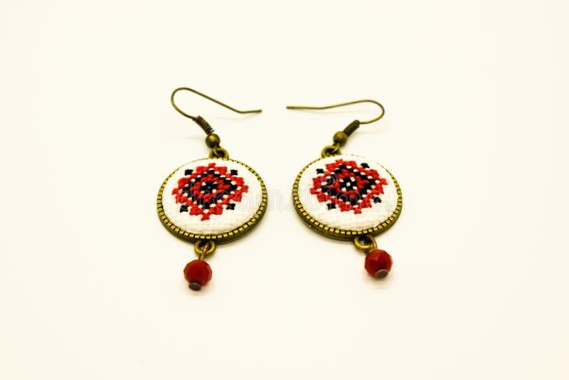 Handgjorda örhängen med den röda och svarta romanian traditionella modellen Isolerat på vit royaltyfri fotografi