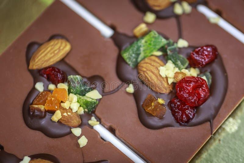 Handgjorda chokladgodisar gjorde från mjölkar choklad som fylldes med muttrar och torkade frukter royaltyfri bild