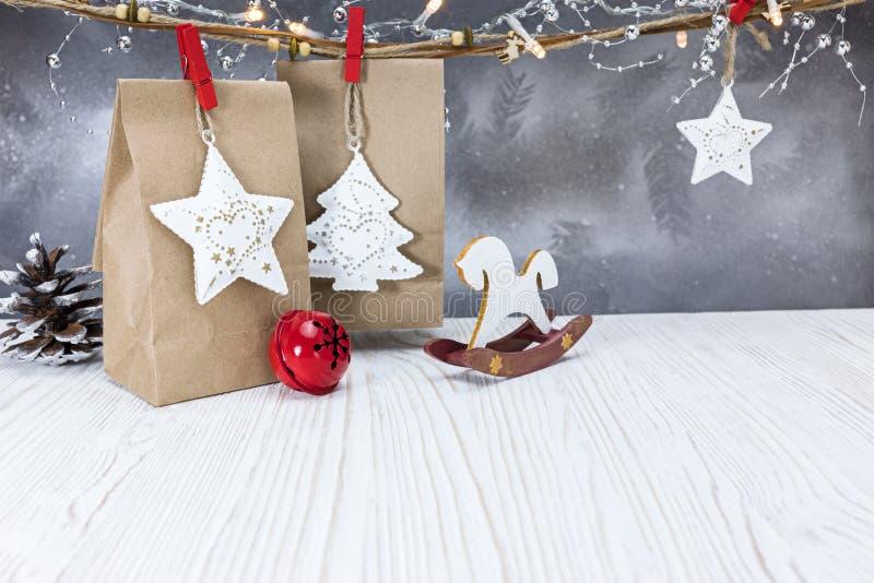 Handgjorda gåvapåsar för jul med garneringar och att glöda garlan arkivbilder
