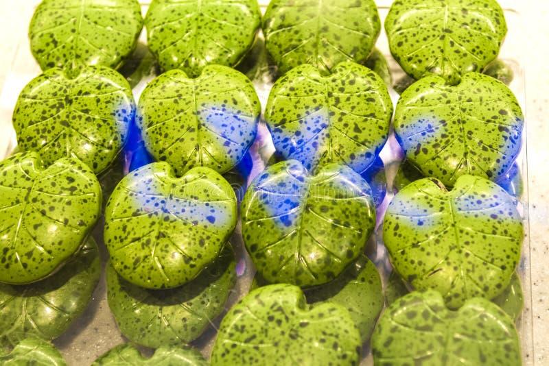 Handgjorda gröna godisar i form av monsterablad på ettfönster shoppar in Smakliga sötsaker Supermarket kafé Ovanlig form fotografering för bildbyråer