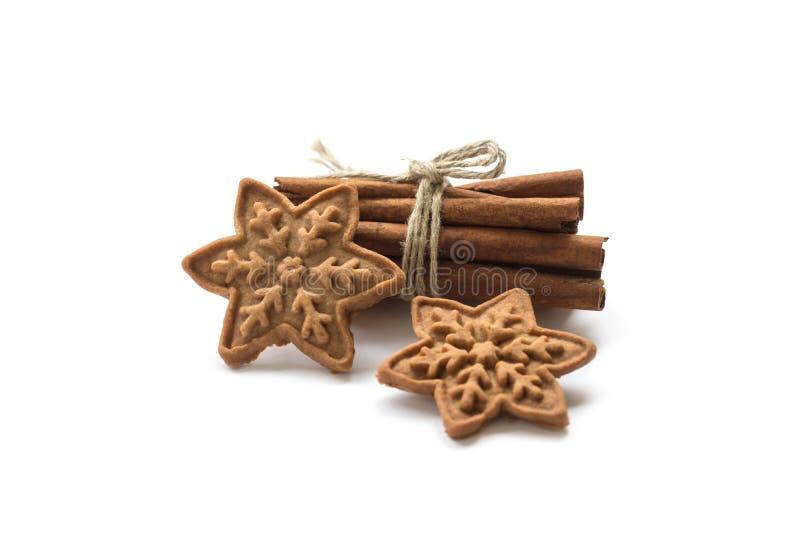 Handgjorda julkakor och kanelbruna pinnar på en vit backgroun arkivbild