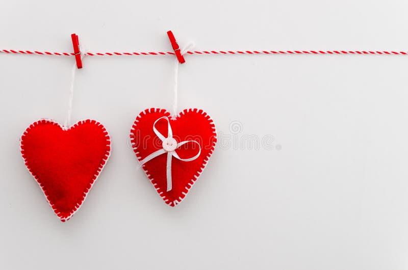 Handgjorda röda hjärtor av filt på ett rep med klädnypan Idé garnering, inbjudningar, plan lekmanna- bästa sikt som är vit royaltyfri foto