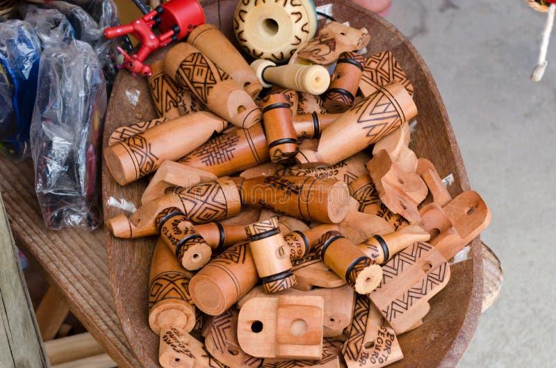 Handgjorda trävisslingar, som efterapar ljud av fåglar, sålde på hemslöjdmässor i Brasilien royaltyfria bilder