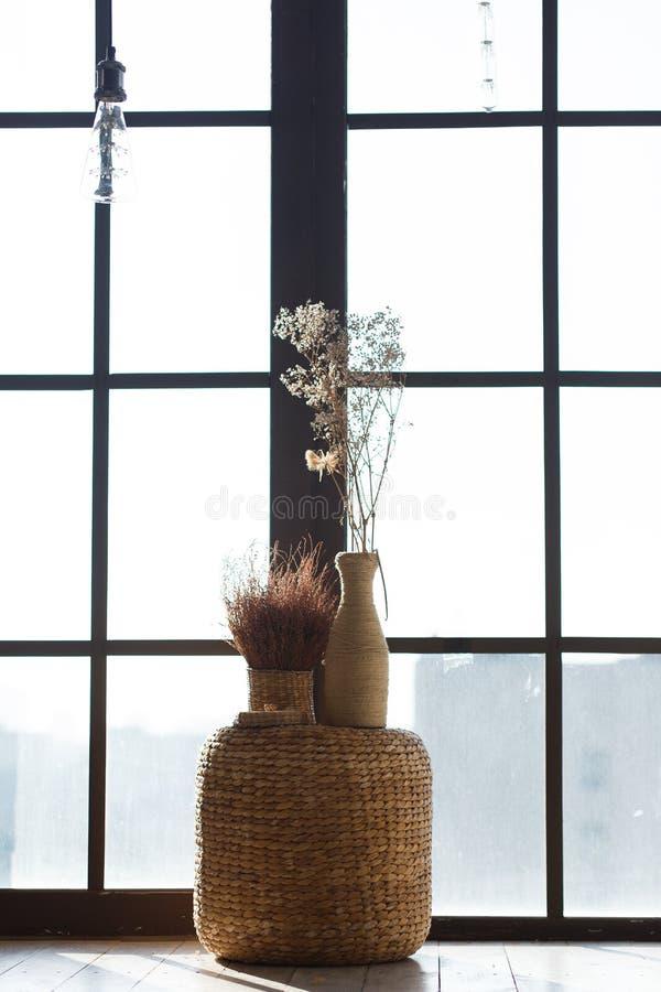 Handgjorda vaser med blommor, stort fönster på bakgrund royaltyfri foto