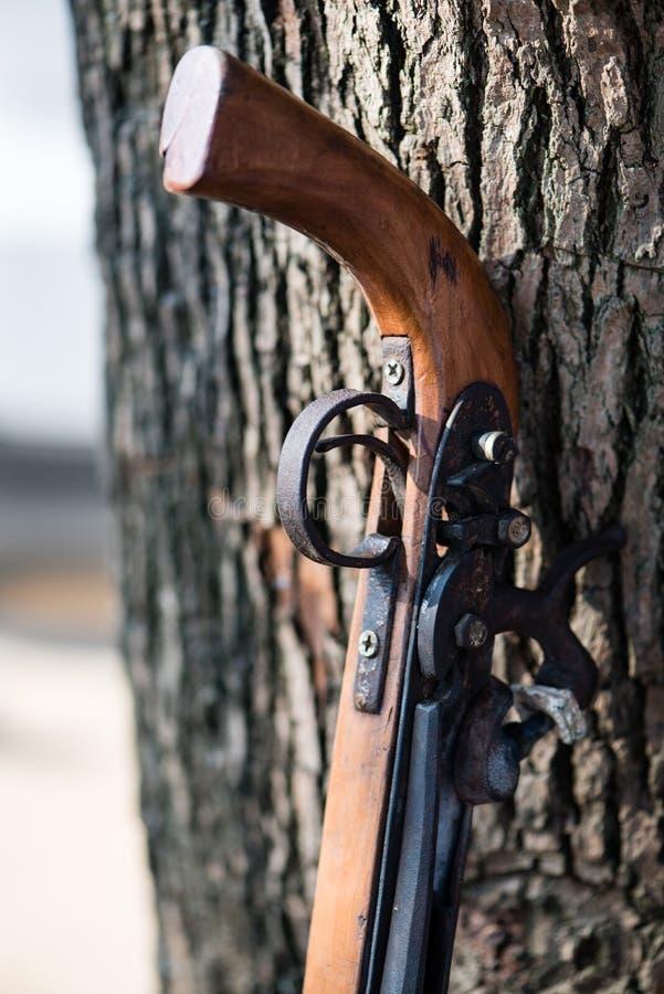 Handgjort gevär av en kinesisk minoritet som vilar mot ett träd arkivbilder