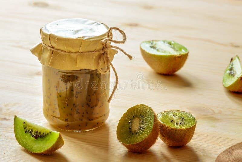 Handgjort grönt sunt kiwidriftstopp som är glassjar med rå tropiska frukter på trätabellbakgrund i solljus arkivbild
