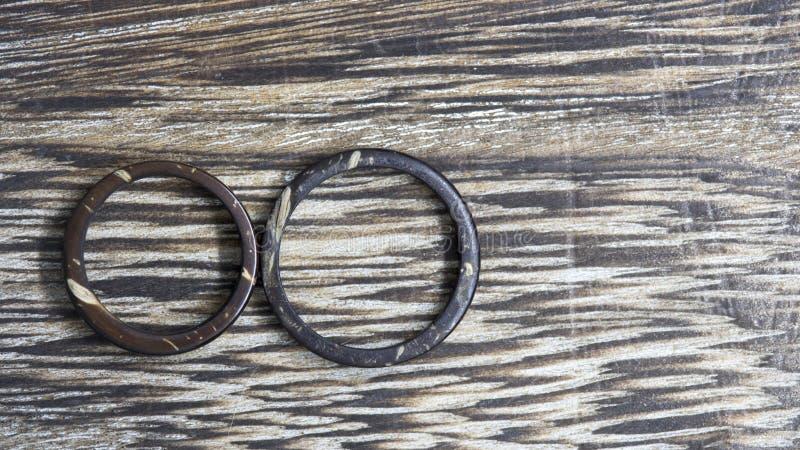 Handgjort hans och hennes kokosnötcirklar i träbakgrund Unikt hantverkarevigselringmusikband Förälskelse och fackligt begrepp royaltyfria bilder
