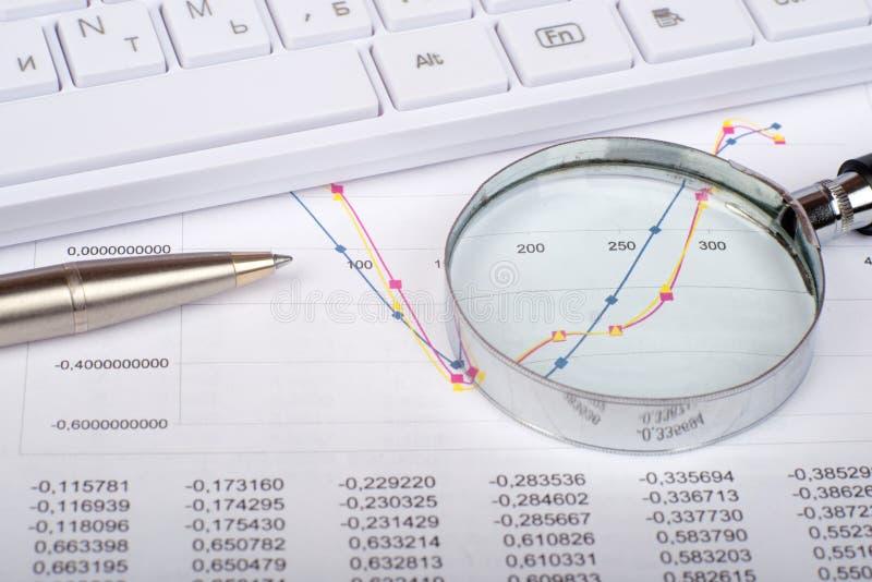 Handglas op documenten met grafieken stock fotografie