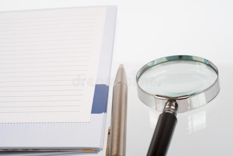 Handglas, pen en notitieboekje stock fotografie