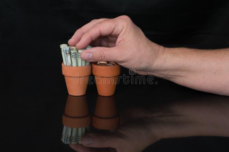 Handgrabbinpengar i en terrakottakruka arkivfoto