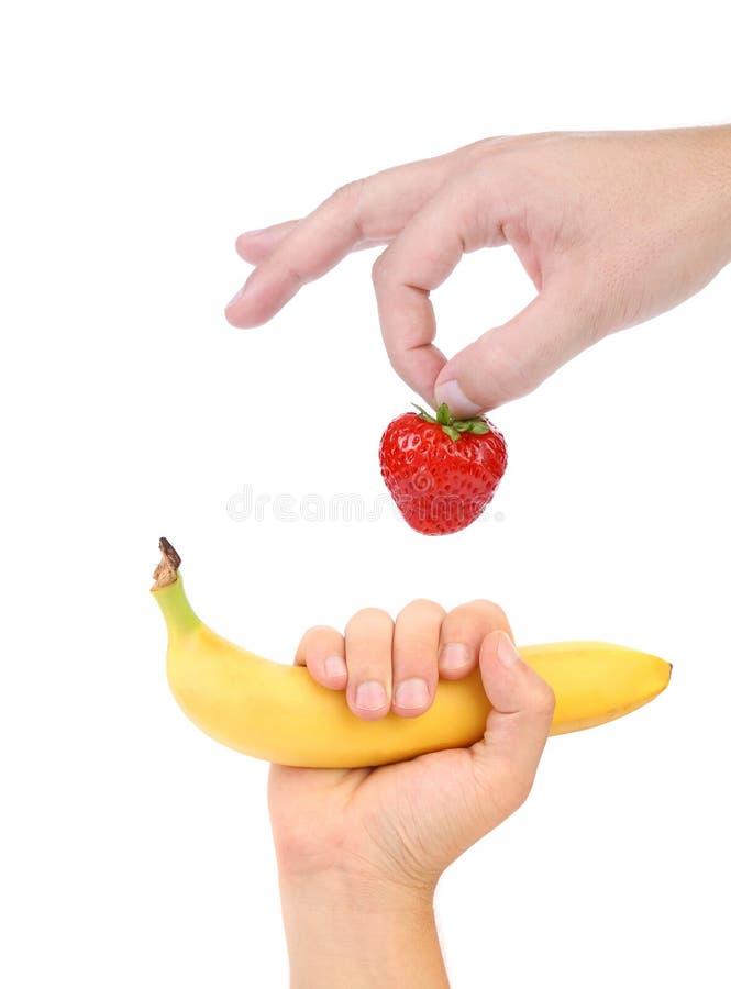 Handgriff Erdbeere und Banane. lizenzfreie stockbilder