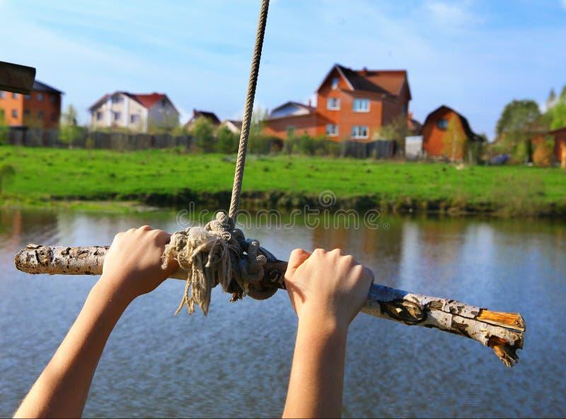 Handgriff-Seilschwingen vor Sprung in das Wasser auf dem hous Hintergrund des Sees und der Villa lizenzfreies stockbild