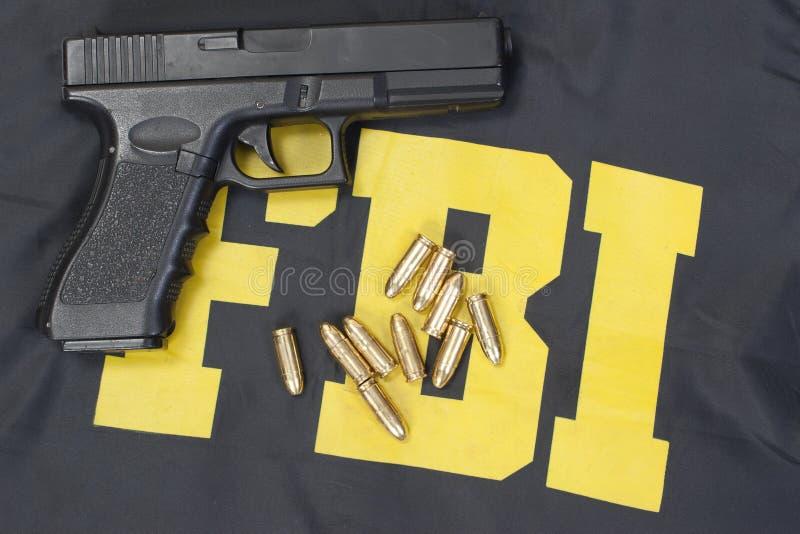 9mm handgun with ammo on fbi uniform. Handgun with ammo on fbi uniform royalty free stock photo