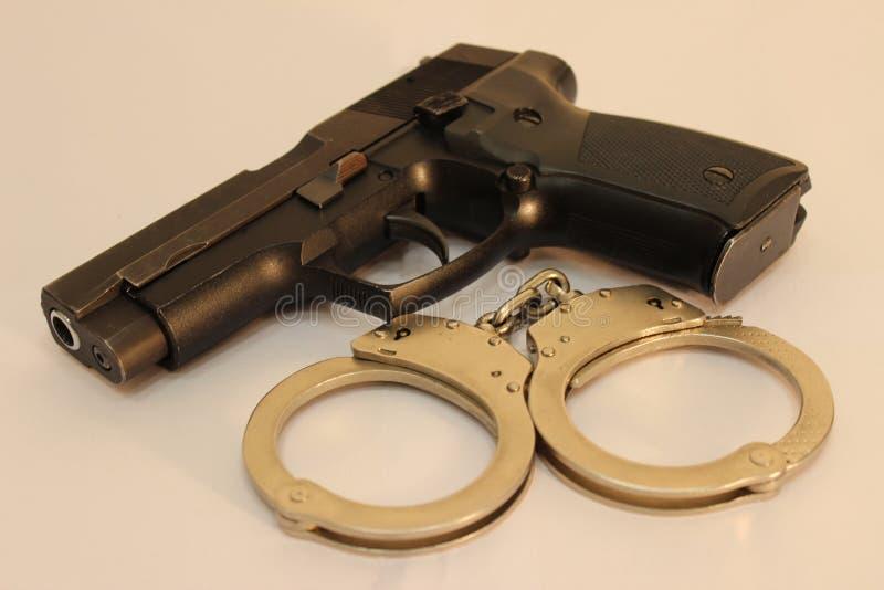 Gun and closed handcuffs, closeup royalty free stock image