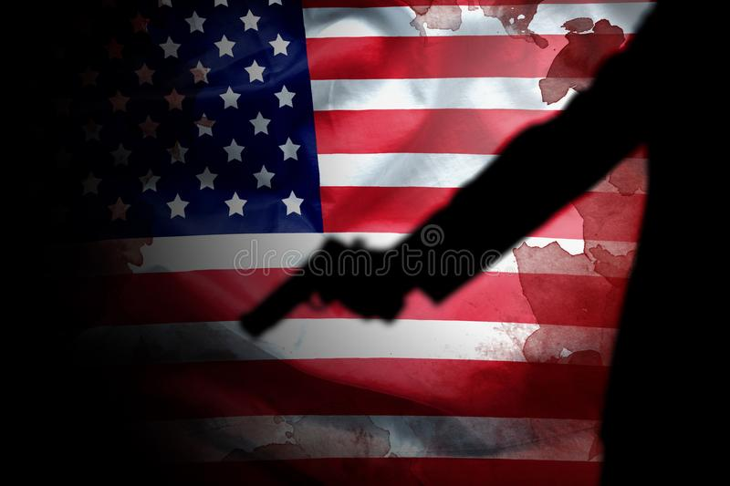 Handgun in gunman hand with blood stain on American flag. stock image