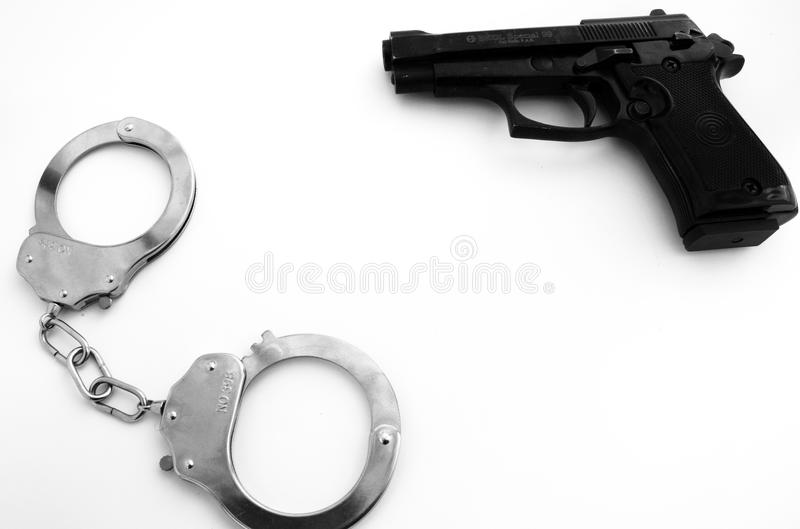 Handgun and handcuffs weapon agression criminal white empty surface, background, concept. royalty free stock photos