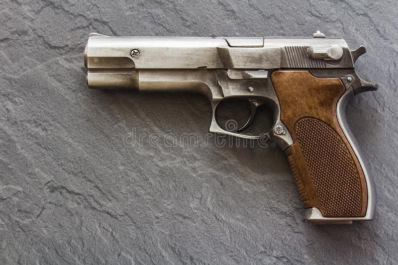 Handgun pistol on dark marble background from side royalty free stock images