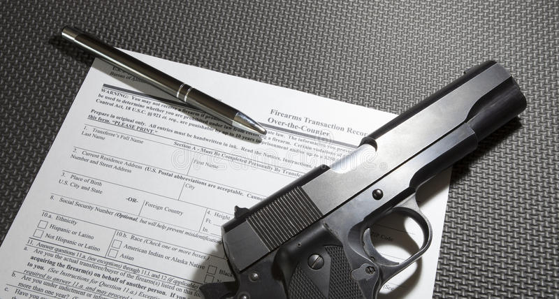 Handgun purchase paperwork. Federal form required to purchase a firearm with a handgun and pen royalty free stock photo